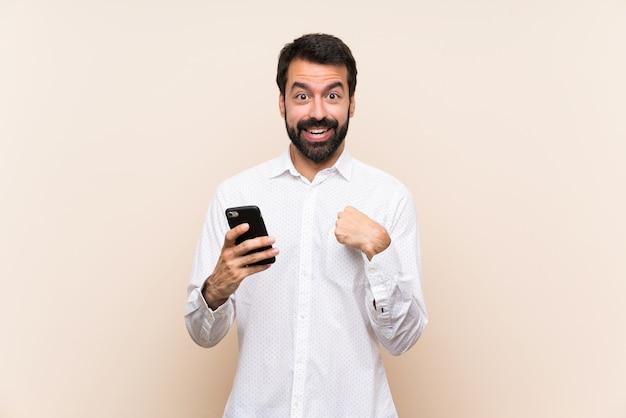 Junger mann mit dem bart, der ein mobile mit überraschungsgesichtsausdruck hält