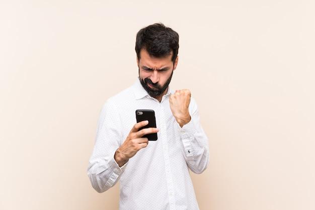 Junger mann mit dem bart, der ein mobile mit verärgerter geste hält