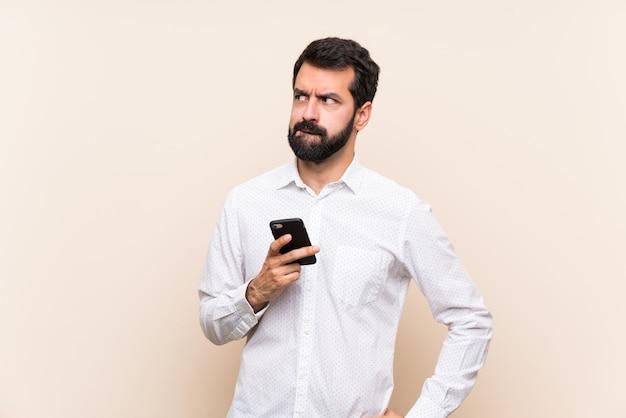 Junger mann mit dem bart, der ein mobile mit verwirrtem gesichtsausdruck hält