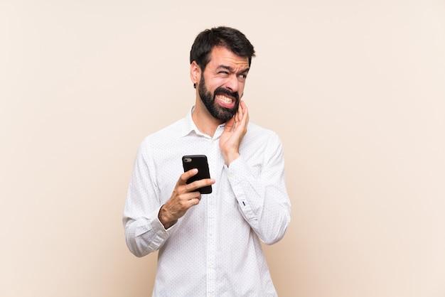Junger mann mit dem bart, der ein mobile mit zahnschmerzen hält