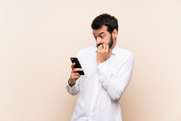 Junger mann mit dem bart, der ein mobile nervös und erschrocken hält, hände zum mund setzend