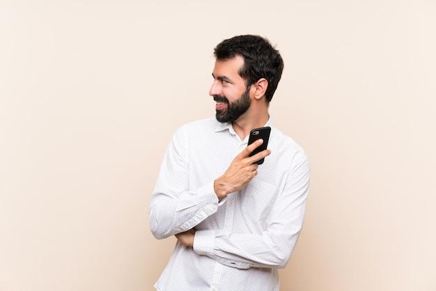 Junger mann mit dem bart, der ein mobile schaut zur seite hält