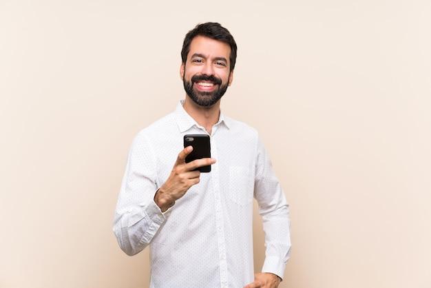 Junger mann mit dem bart, der ein mobile sendet eine mitteilung mit dem mobile hält