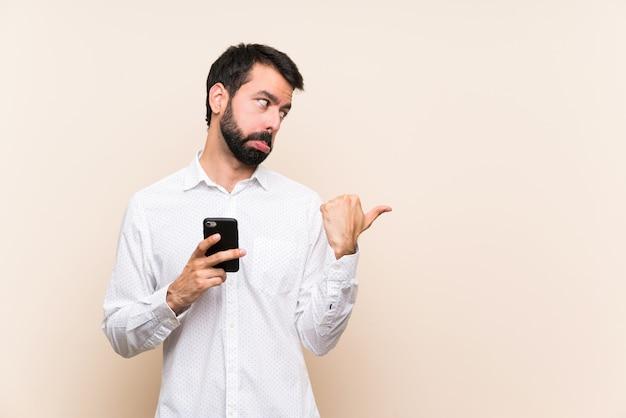Junger mann mit dem bart, der ein mobile unglücklich hält und auf die seite zeigt