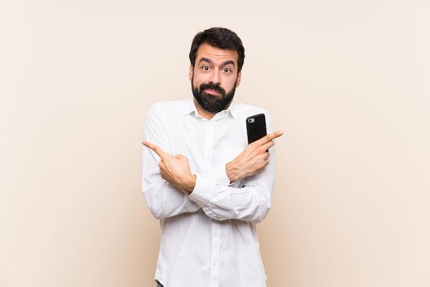 Junger mann mit dem bart, der ein mobile zeigt auf die seitenteile hat zweifel hält