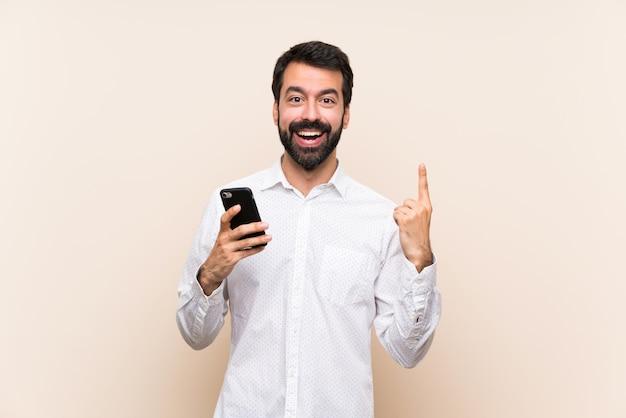 Junger mann mit dem bart, der ein mobile zeigt herauf eine großartige idee hält