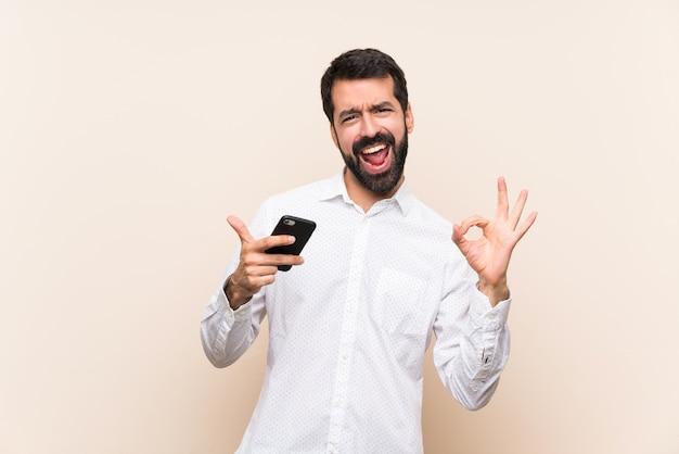 Junger mann mit dem bart, der ein mobile zeigt okayzeichen und daumen herauf geste hält
