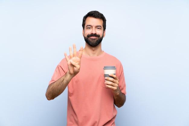 Junger mann mit dem bart, der einen mitnehmerkaffee auf blauem glücklichem hält und vier mit den fingern zählt