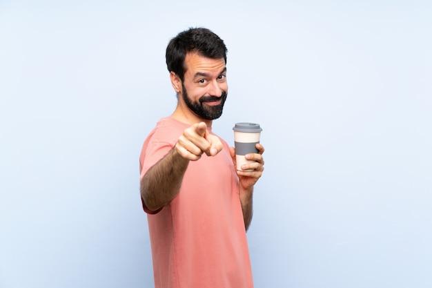 Junger mann mit dem bart, der einen mitnehmerkaffee auf finger der blauen punkte auf sie mit einem überzeugten ausdruck hält