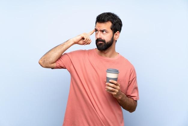 Junger mann mit dem bart, der einen mitnehmerkaffee über dem lokalisierten blau hat zweifel und das denken hält