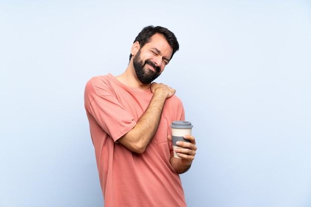 Junger mann mit dem bart, der einen mitnehmerkaffee über dem lokalisierten blau leidet unter den schmerz in der schulter hält