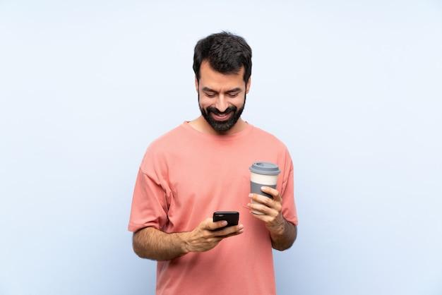 Junger mann mit dem bart, der einen mitnehmerkaffee über dem lokalisierten blau sendet eine mitteilung mit dem mobile hält