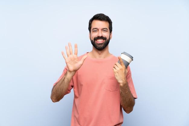 Junger mann mit dem bart, der einen mitnehmerkaffee über dem lokalisierten blau zählt sechs mit den fingern hält