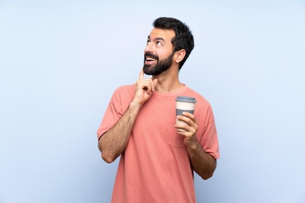 Junger mann mit dem bart, der einen mitnehmerkaffee über der lokalisierten blauen wand denkt eine idee beim oben schauen hält