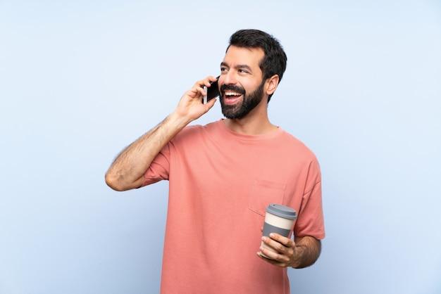 Junger mann mit dem bart, der einen mitnehmerkaffee über der lokalisierten blauen wand hält ein gespräch mit dem handy hält