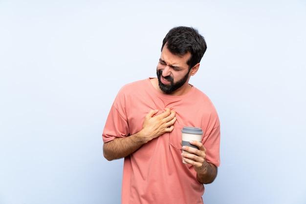 Junger mann mit dem bart, der einen mitnehmerkaffee über der lokalisierten blauen wand hat schmerz im herzen hält