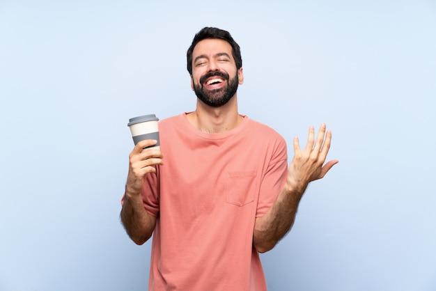 Junger mann mit dem bart, der einen mitnehmerkaffee über der lokalisierten blauen wand lächelt viel hält