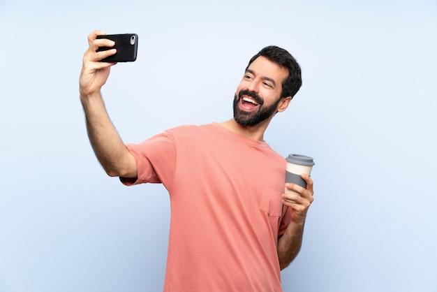 Junger mann mit dem bart, der einen mitnehmerkaffee über der lokalisierten blauen wand macht ein selfie hält
