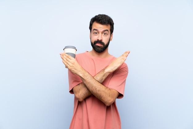 Junger mann mit dem bart, der einen mitnehmerkaffee über der lokalisierten blauen wand macht keine geste hält