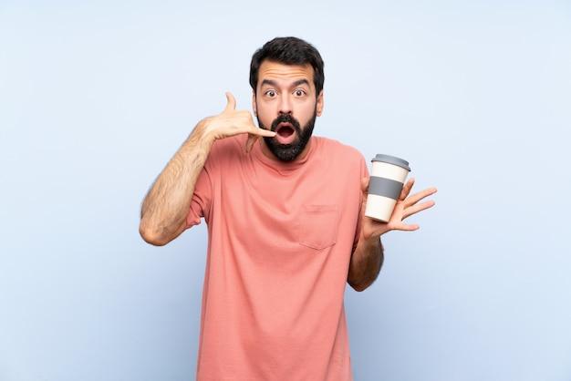 Junger mann mit dem bart, der einen mitnehmerkaffee über der lokalisierten blauen wand macht telefongeste und das zweifeln hält