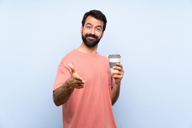 Junger mann mit dem bart, der einen mitnehmerkaffee über der lokalisierten blauen wand rüttelt hände für das schließen viel hält