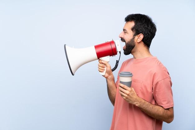 Junger mann mit dem bart, der einen mitnehmerkaffee über der lokalisierten blauen wand schreit durch ein megaphon hält