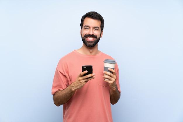 Junger mann mit dem bart, der einen mitnehmerkaffee über der lokalisierten blauen wand sendet eine mitteilung mit dem mobile hält