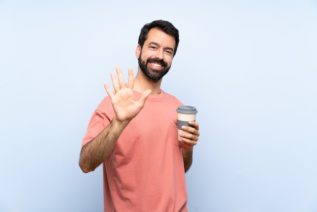 Junger mann mit dem bart, der einen mitnehmerkaffee über der lokalisierten blauen wand zählt fünf mit den fingern hält
