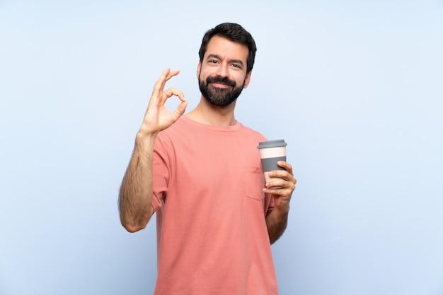 Junger mann mit dem bart, der einen mitnehmerkaffee über der lokalisierten blauen wand zeigt okayzeichen mit den fingern hält