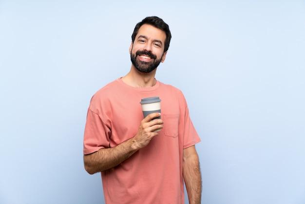 Junger mann mit dem bart, der einen mitnehmerkaffee über getrenntem blauem lachen anhält