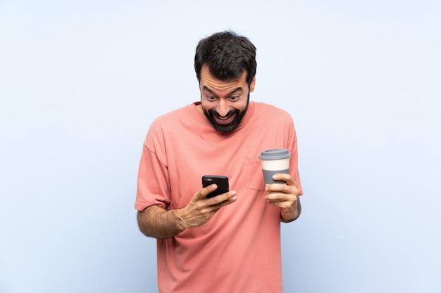 Junger mann mit dem bart, der einen mitnehmerkaffee über lokalisiertem blau hält, überraschte und eine mitteilung sendend