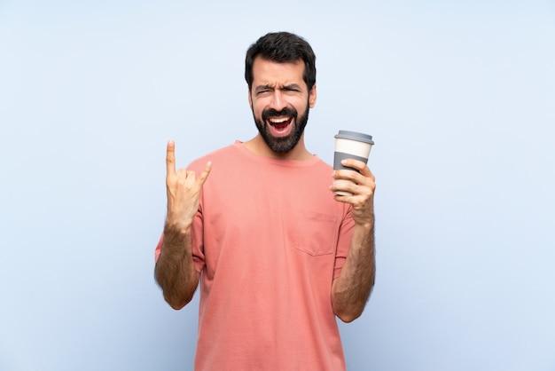 Junger mann mit dem bart, der einen mitnehmerkaffee über lokalisiertem blau macht felsengeste hält