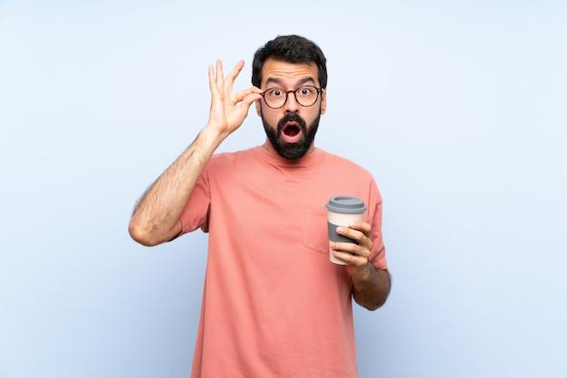 Junger mann mit dem bart, der einen mitnehmerkaffee über lokalisiertem blau mit gläsern und überrascht hält