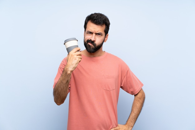Junger mann mit dem bart, der einen mitnehmerkaffee über lokalisiertem blau mit verärgerter geste hält