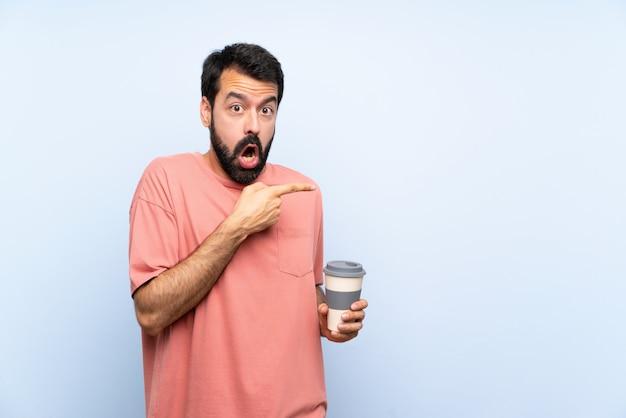 Junger mann mit dem bart, der einen mitnehmerkaffee über lokalisiertem blau überrascht hält und seite zeigt