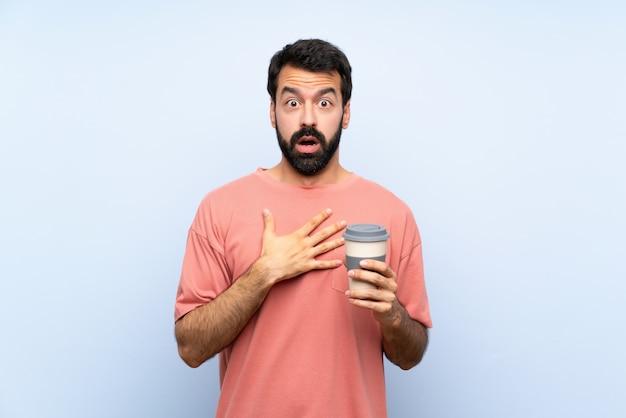 Junger mann mit dem bart, der einen mitnehmerkaffee über lokalisiertem blau überrascht und beim schauen entsetzt hält