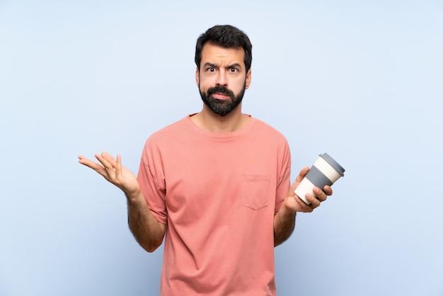 Junger mann mit dem bart, der einen mitnehmerkaffee über lokalisiertem blau unglücklich für hält, verstehen etwas nicht