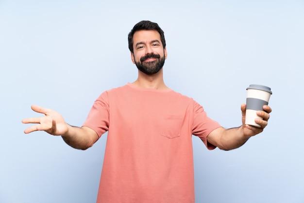 Junger mann mit dem bart, der einen mitnehmerkaffee über lokalisiertem blauem darstellen hält und einlädt, mit der hand zu kommen
