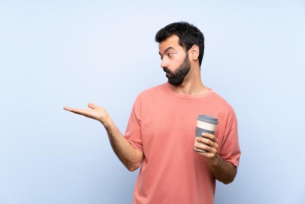 Junger mann mit dem bart, der einen mitnehmerkaffee über lokalisiertem blauem haltenem copyspace mit zweifeln hält