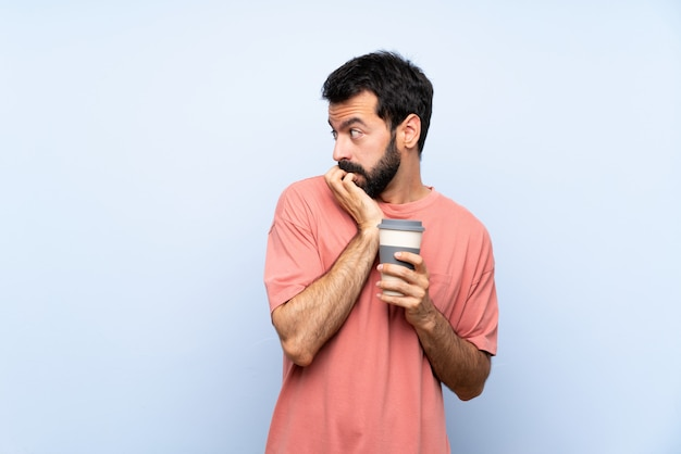 Junger mann mit dem bart, der einen mitnehmerkaffee über lokalisiertem blauem nervösem und erschrockenem setzendem hände zum mund hält