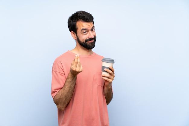 Junger mann mit dem bart, der einen mitnehmerkaffee über lokalisierter blauer verdienstgeldgeste hält