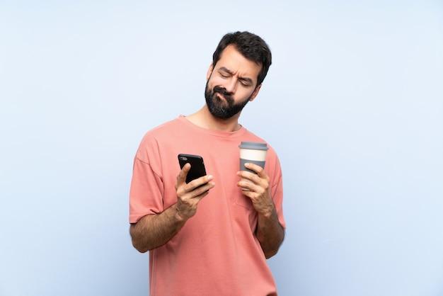 Junger mann mit dem bart, der einen mitnehmerkaffee über lokalisierter blauer wand denkt und sendet eine mitteilung hält