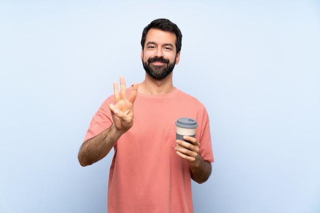Junger mann mit dem bart, der einen mitnehmerkaffee über lokalisierter blauer wand glücklich hält und drei mit den fingern zählt