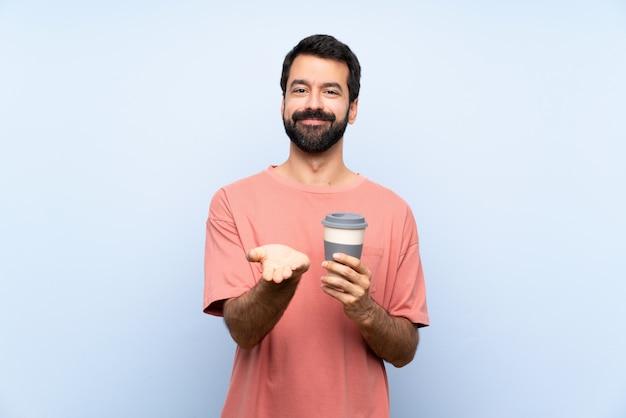 Junger mann mit dem bart, der einen mitnehmerkaffee über lokalisierter blauer wand hält copyspace eingebildet auf der palme hält, um eine anzeige einzufügen