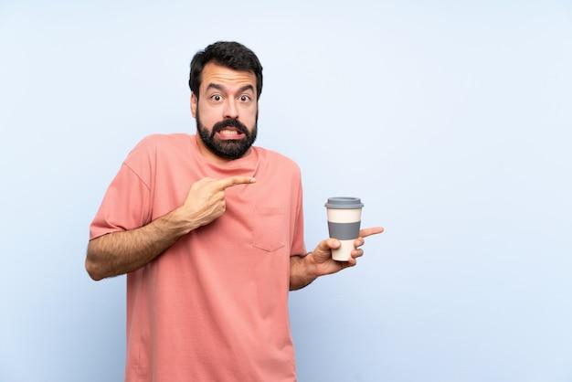 Junger mann mit dem bart, der einen mitnehmerkaffee über lokalisierter blauer wand hält, erschrak und zeigte auf die seite