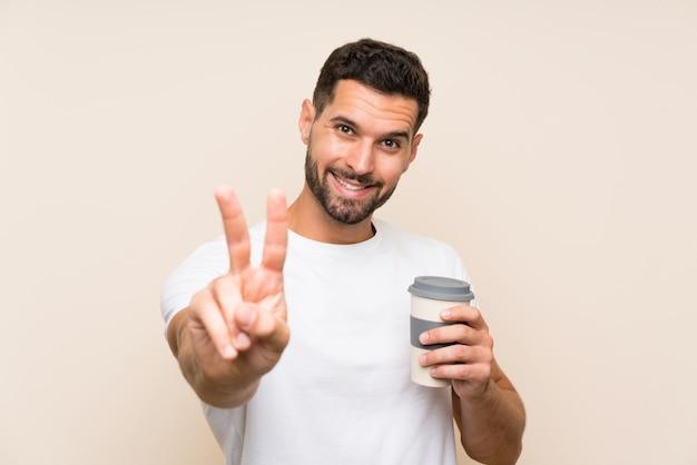 Junger mann mit dem bart, der einen mitnehmerkaffee über lokalisierter blauer wand lächelt und zeigt siegeszeichen hält