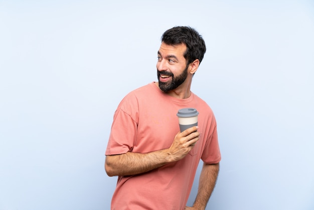 Junger mann mit dem bart, der einen mitnehmerkaffee über lokalisierter blauer wand mit den armen gekreuzt und glücklich hält