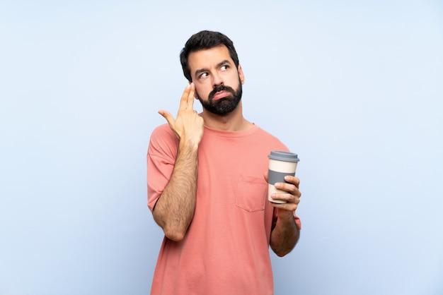 Junger mann mit dem bart, der einen mitnehmerkaffee über lokalisierter blauer wand mit den problemen machen selbstmordgeste hält