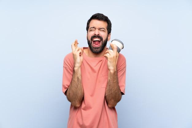 Junger mann mit dem bart, der einen mitnehmerkaffee über lokalisierter blauer wand mit der fingerüberfahrt hält