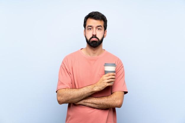 Junger mann mit dem bart, der einen mitnehmerkaffee über lokalisierter blauer wand mit traurigem und deprimiertem ausdruck hält